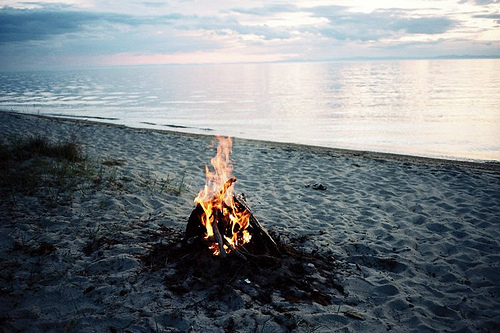 camp_fire_on_beach_still_water_and_sand